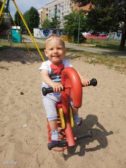uśmiechnięte dziecko siedzi na koniku na placu zabaw