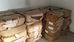 paczki z nielegalnym tytoniem leżą ułożone w pomieszczeniu gospodarczym pod scianą