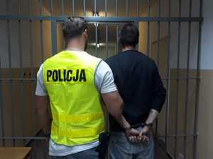policjant idzie z zatrzymanym mezczyzna