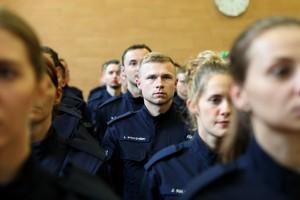Nowo przyjęty policjant stoi w tłumie adeptów