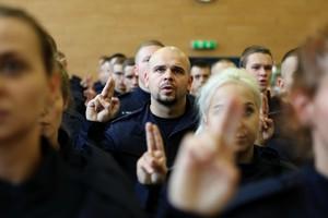 Nowo przyjęty policjant stoi w tłumie adeptów i ślubuje