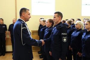 Komendant Wojewódzki Policji w Poznaniu insp. Piotr Mąka w galowym mundurze wita się z młodym nowo przyjętym policjantem