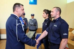 Komendant Wojewódzki Policji w Poznaniu insp. Piotr Mąka w galowym mundurze gratuluje policjantowi