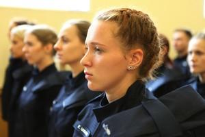 Nowo przyjęty policjantka stoi w tłumie adeptów