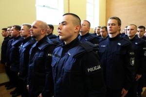 Nowo przyjęci policjanci stoją w tłumie adeptów