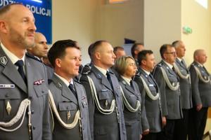 Kadra kierownicza wielkopolskiej Policji stoi w galowych mundurach w rzędzie
