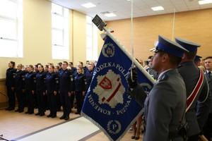 Poczet sztandarowy prezentuje sztandar, w tle nowo przyjęci policjanci