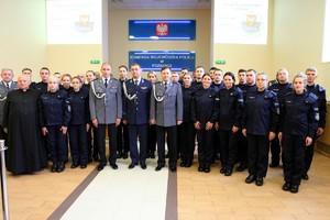 Komendant Wojewódzki Policji w Poznaniu wraz z zastępcami pozuje do grupowego zdjęcia z nowo przyjętymi policjantami