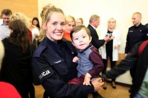 Policjantka trzyma na rękach małe dziecko